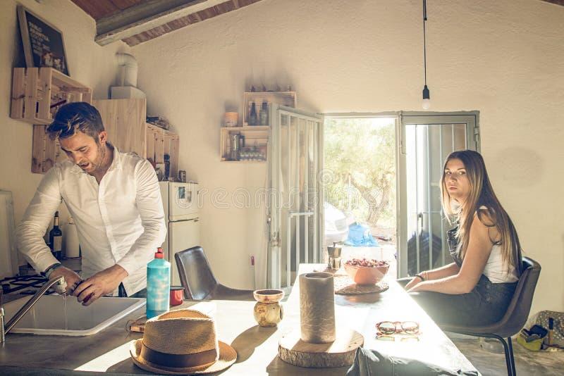 Пара в кухне и человеке делая блюда Концепция сотрудничества в паре стоковые фотографии rf