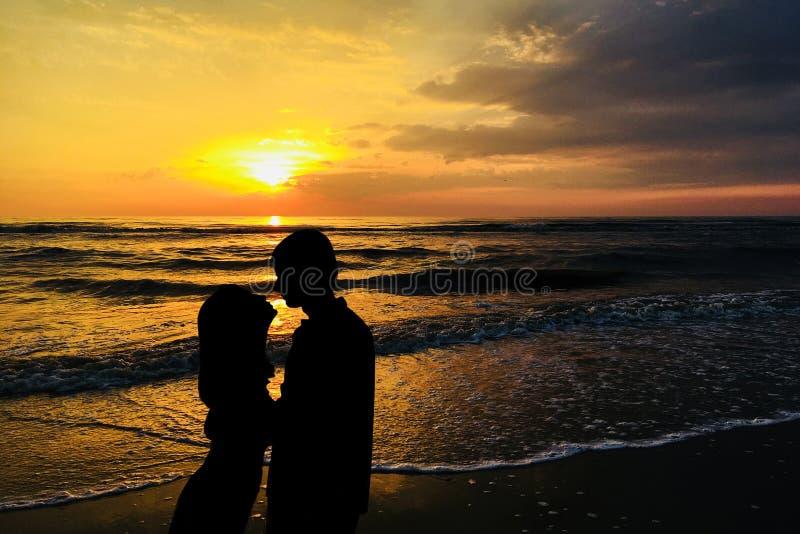 Пара в любов целует против захода солнца стоковые фотографии rf