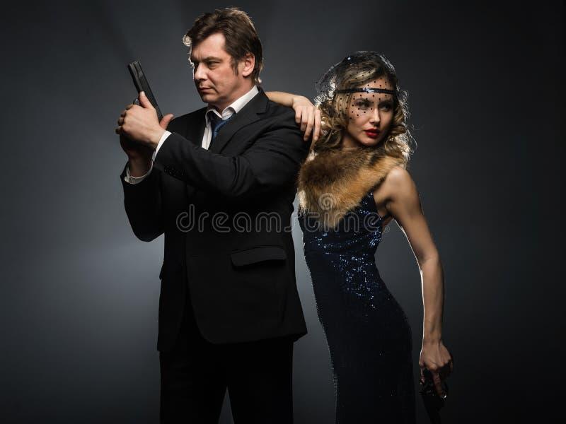 Пара гангстеров, человека и женщины с оружи стоковые изображения