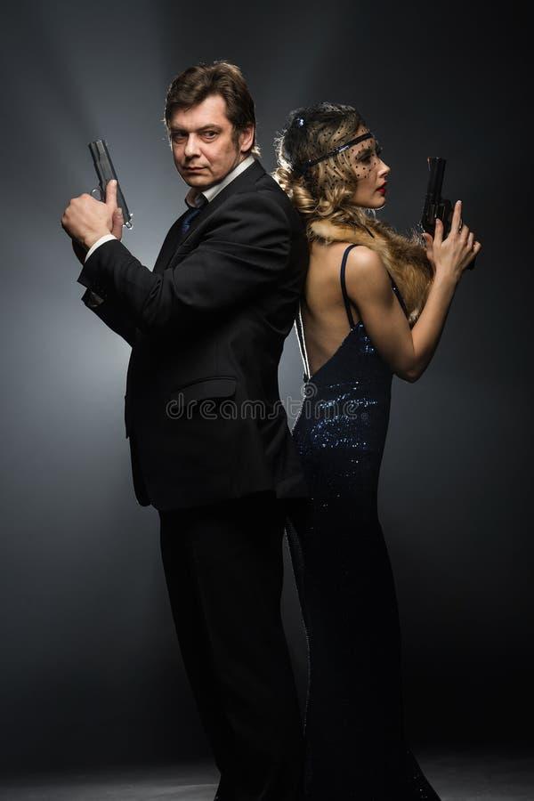 Пара гангстеров, человека и женщины с оружи стоковая фотография rf