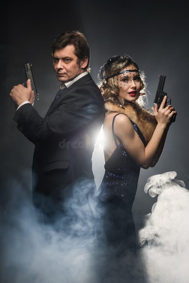 Пара гангстеров, человека и женщины с оружи стоковая фотография