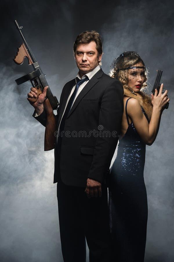 Пара гангстеров, человека и женщины с оружи стоковые фото