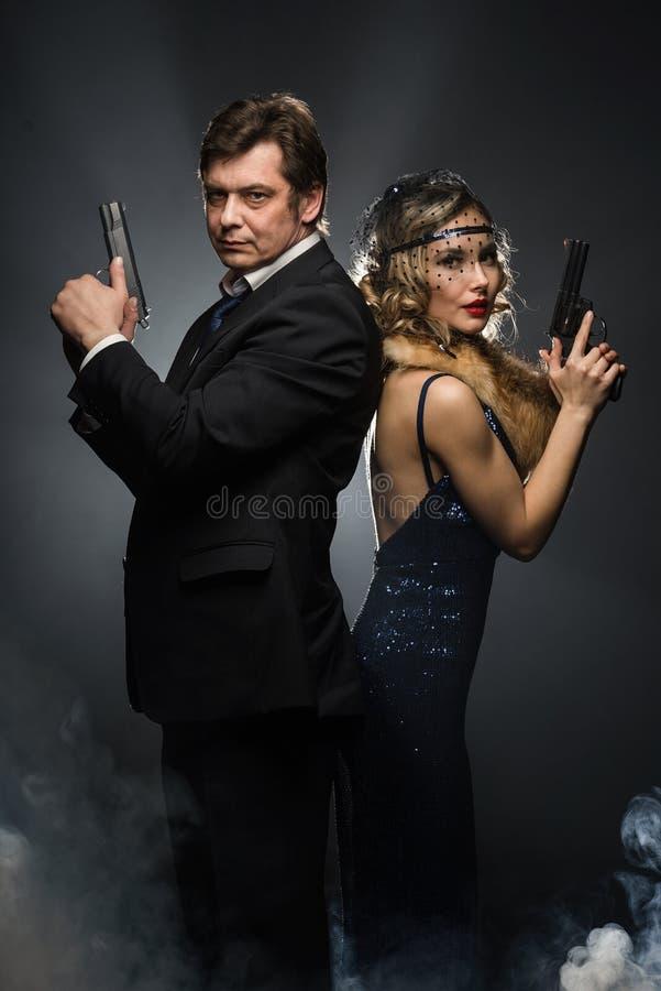 Пара гангстеров, человека и женщины с оружи стоковое фото rf