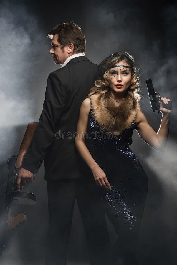 Пара гангстеров, человека и женщины с оружи стоковое изображение rf