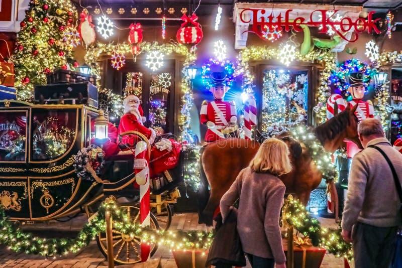 Пара делает паузу для того чтобы восхитить украшения рождества на маленьком Kook - кафе сказки тематическом продавая помадки стоковая фотография