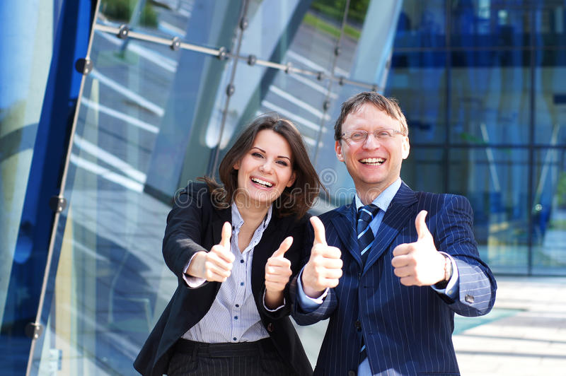 Пара дела в официально одеждах держа большие пальцы руки стоковое изображение rf