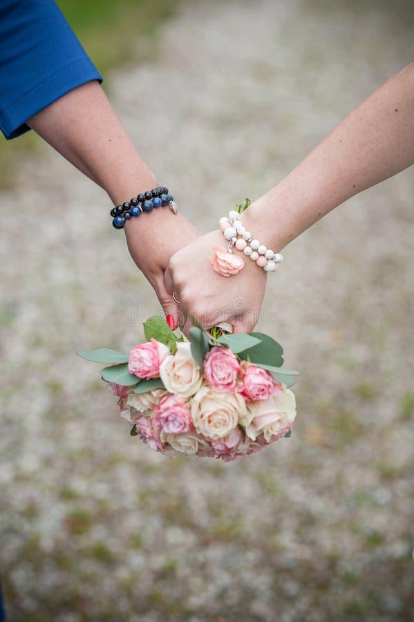 Пара держит руку с букетом цветка свадьбы стоковые изображения rf