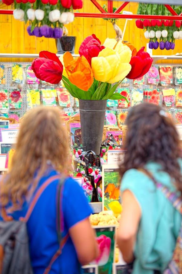 Пара девушек смотрит гигантские тюльпаны на Bloemenmarkt Амстердаме стоковые фотографии rf