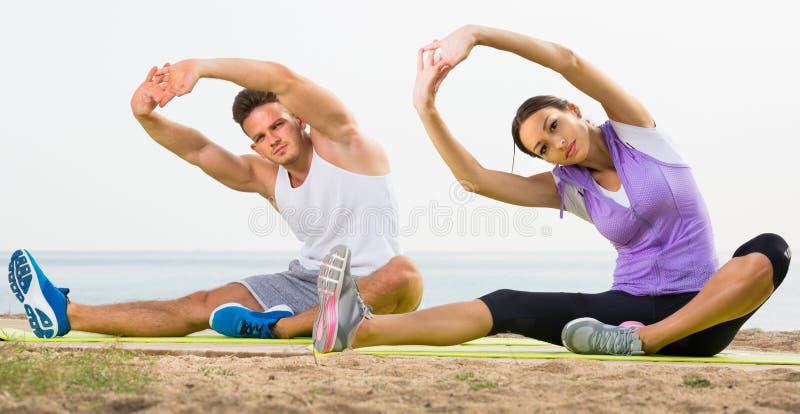 Пара делая йогу представляет сидеть на пляже моря стоковые изображения rf
