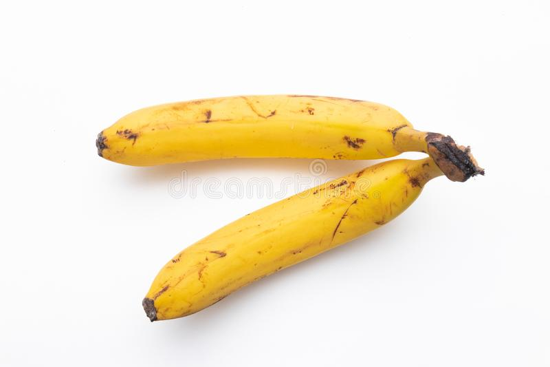 Пара зрелых бананов на белой предпосылке 2 банана перезрелы и прикреплены к черенок Они имеют коричневый цвет и слепые пятна стоковая фотография rf