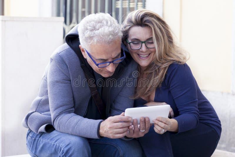 Пара зрелых людей советует с smartphone стоковые изображения rf