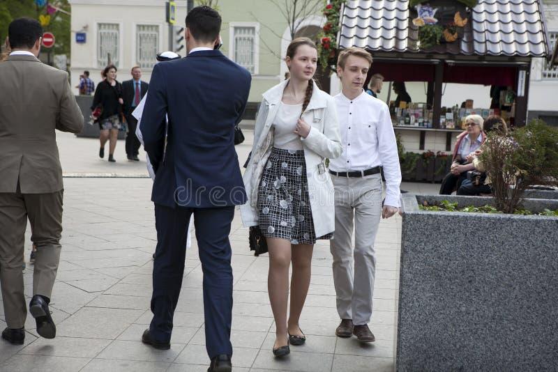 Пара идет вниз с улицы Девушка носит checkered серую юбку и белую блузку Молодой человек в белой классической рубашке стоковые изображения