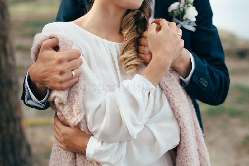 Пара любовников держит руки одина другого на заднем плане природы стоковое фото rf