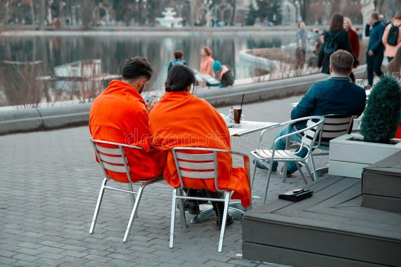 Пара любовников покрытых с оранжевыми одеялами сидит на стенде около кафа лета в парке Gorky стоковое фото