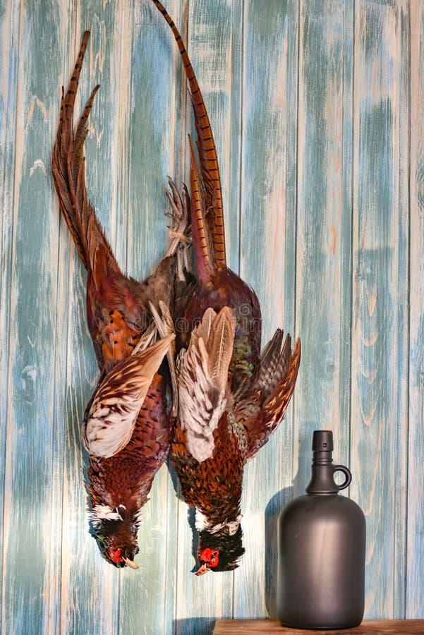 Пара мужских фазанов и boottle на старой деревянной предпосылке Сезон звероловства Скопируйте затир Полная величина стоковые фотографии rf
