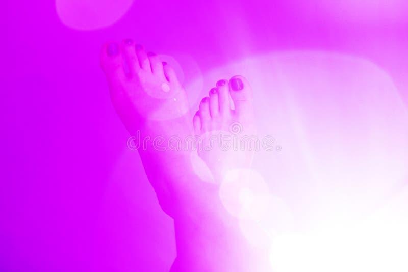 Пара ноги женщин на розовой предпосылке цвета со светами круглыми эффекта ореола стоковое изображение rf