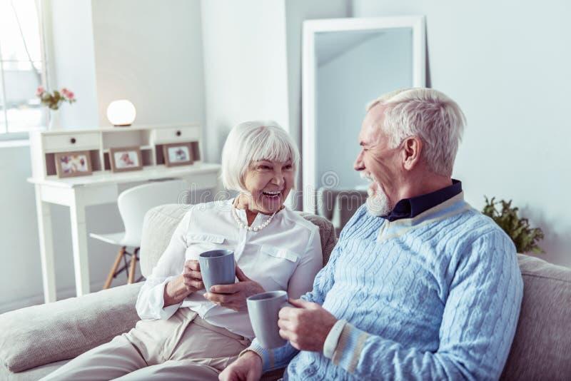 Пара пенсионеров, счастливо наслаждающихся чаем вместе стоковая фотография rf