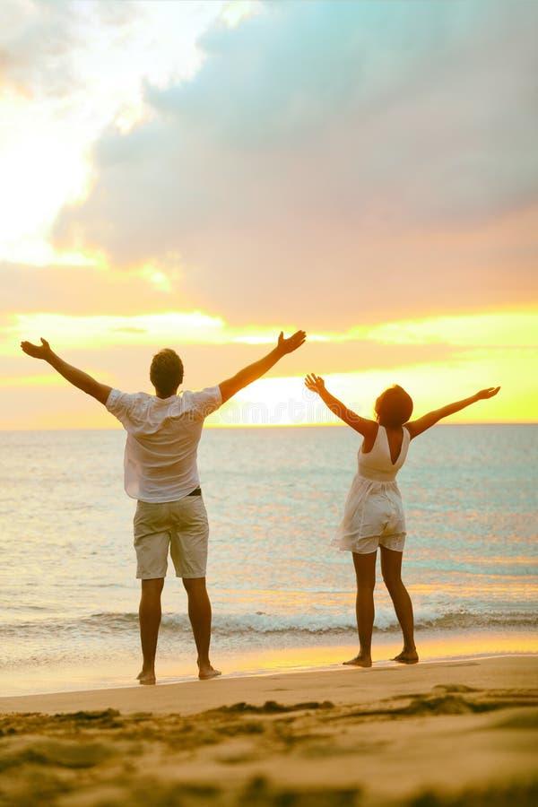 Пара пляжей Sunset с распростертыми объятиями восхваляет свободу в успехе умение, духовность, вера, беззаботность стоковое изображение