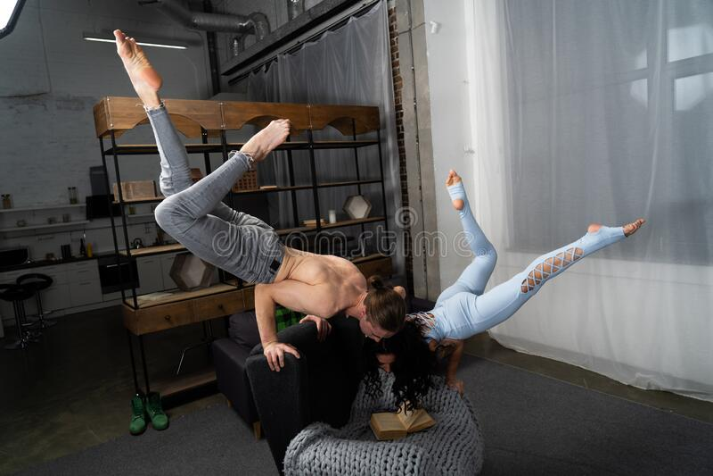 Пара проводит время вместе, читая книгу и делая акробатический баланс дома концепция саморазвития и стоковое изображение rf