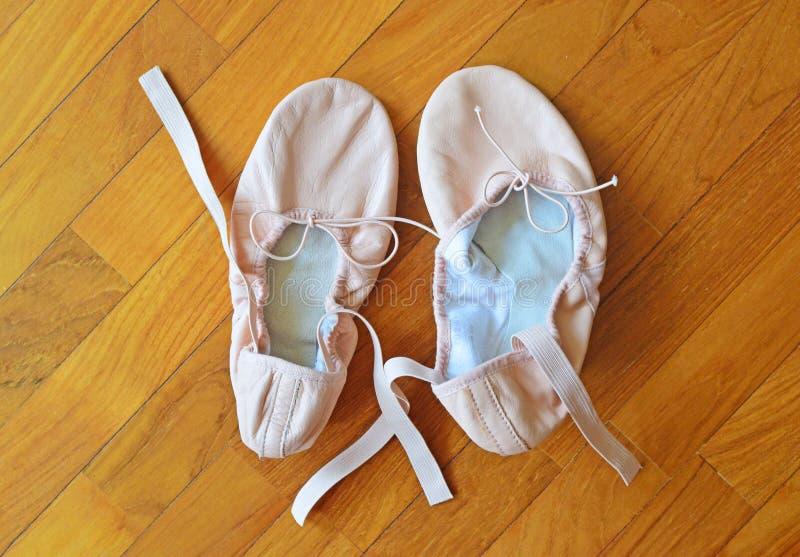 Пара розовых ботинок балета на паркетных полах стоковое фото rf
