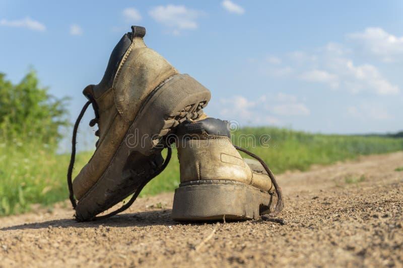 Пара старых изношенных походных ботинок и гравийная тропа стоковые фотографии rf