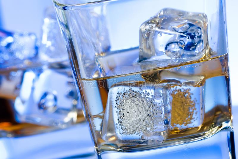 Пара стекел алкогольного напитка с льдом на сини диско освещает стоковое фото rf