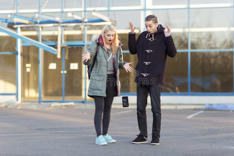 Пара стоит на улице и при отвлекать и возмущенный вид наблюдая smartphone который падает на асфальт стоковые изображения