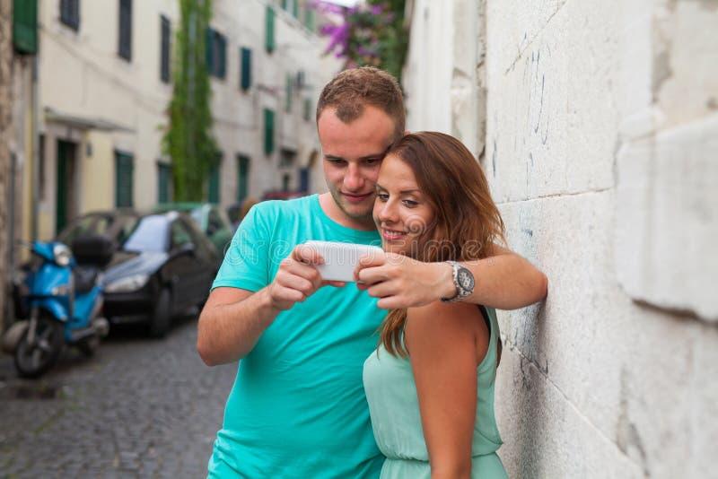 Пара стоя на улице и используя smartphone стоковые изображения