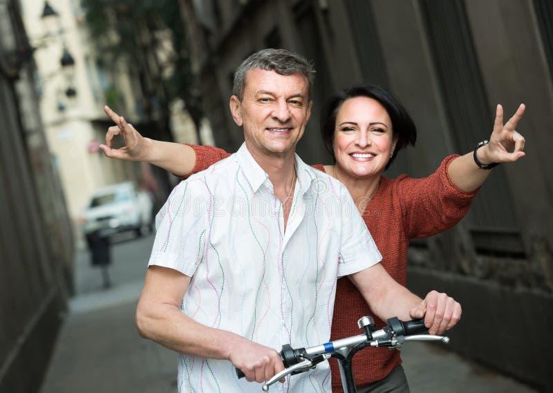 Пара с electrkc велосипед в каникулах на улице города стоковое изображение