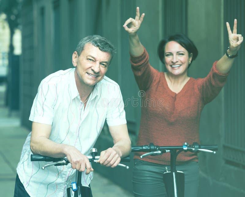 Пара с electrkc велосипед в каникулах на улице города стоковые изображения rf