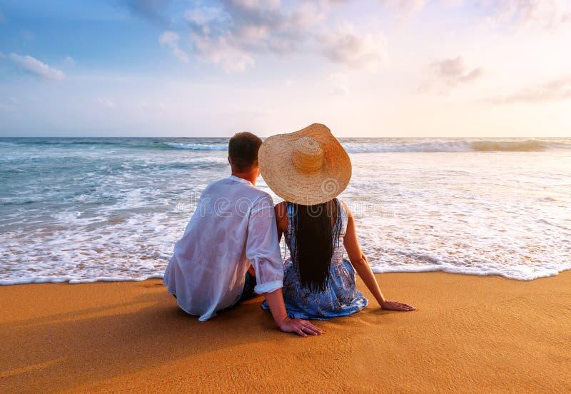 Пара усажена на пляж океана стоковые фотографии rf