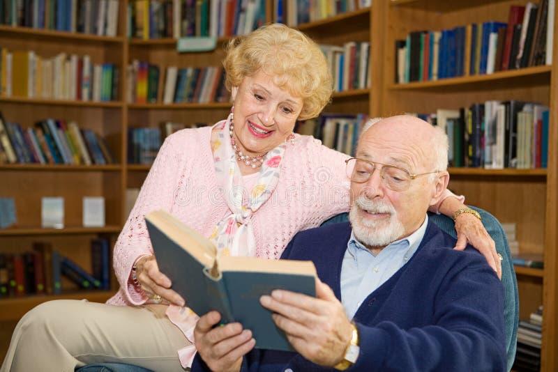 пара читает старший совместно стоковое фото