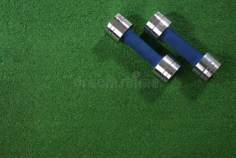 Пара dumbells на предпосылке травы стоковые изображения rf