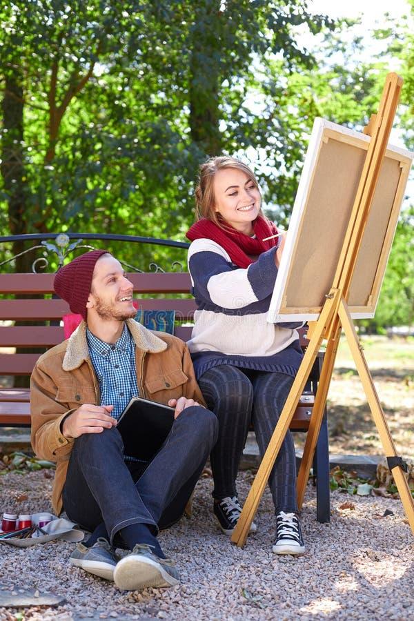 Парень выглядеть как девушка рисует художника стоковое фото