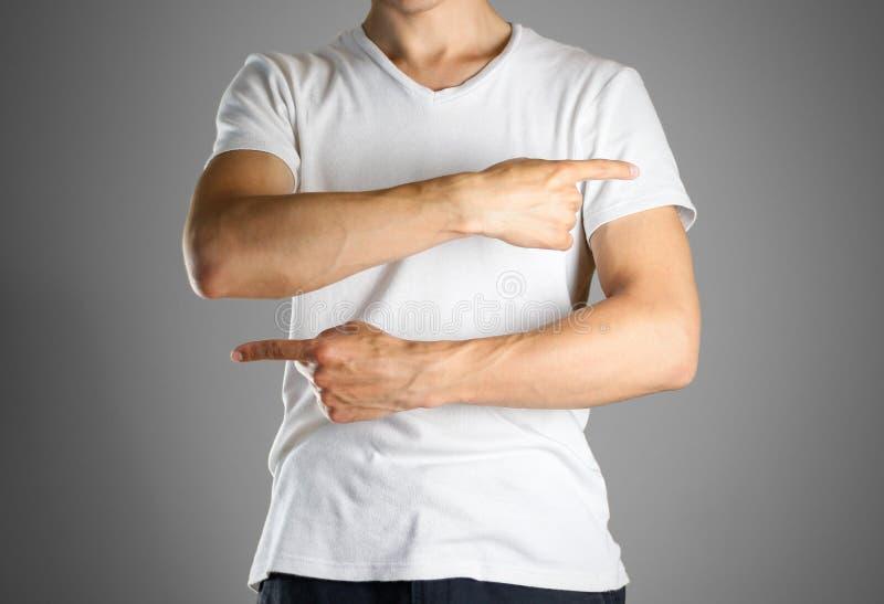 Парень в белой футболке указывая пальцы справедливо и налево определите стоковые изображения rf