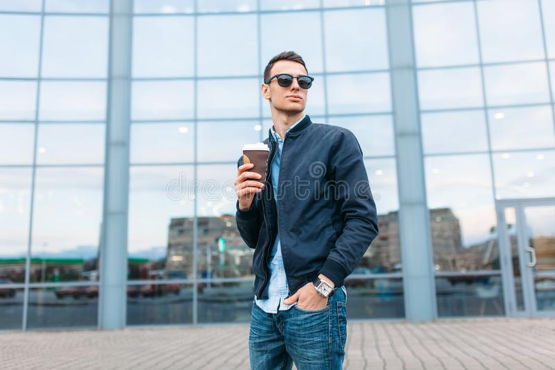 Парень в стильных солнечных очках, человек идет вокруг города и выпивая кофе от бумажного стаканчика, красивый парень идет вокруг стоковое изображение rf