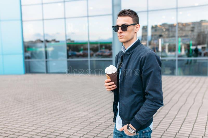 Парень в стильных солнечных очках, человек идет вокруг города и выпивая кофе от бумажного стаканчика, красивый парень идет вокруг стоковые изображения