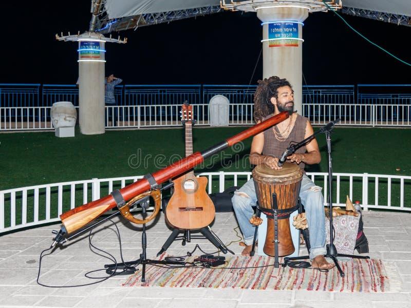 Парень детенышей играет darbuka в вечере на портовом районе в городе Нагарии, в Израиле стоковые фото