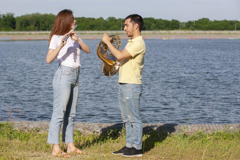 Парень играя рожок и девушку играя каннелюру на озере стоковая фотография rf