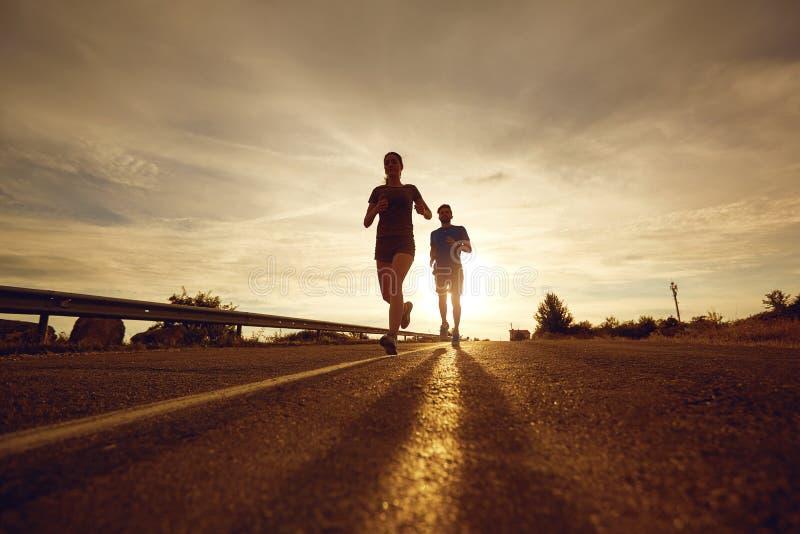 Парень и девушка jog вдоль дороги на заходе солнца в природе стоковые изображения rf