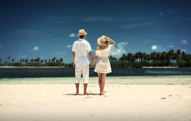 Парень и девушка в белых одеждах на береге острова Мальдивские острова белизна песка Guraidhoo стоковая фотография rf