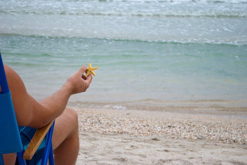 Парень молодого человека сидя на deckchair на береге держа желтую морскую звёзду в его руке стоковые фото