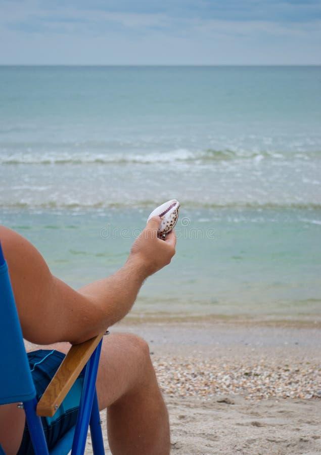 Парень молодого человека сидя на deckchair на береге держа желтую морскую звёзду в его руке стоковые фотографии rf