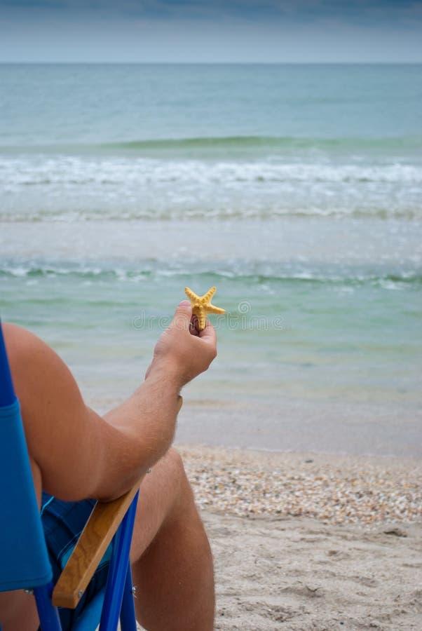 Парень молодого человека сидя на deckchair на береге держа желтую морскую звёзду в его руке стоковые изображения rf