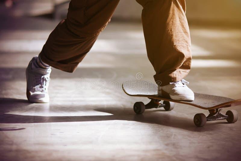 Парень нажимает с пола и едет скейтборд стоковое изображение