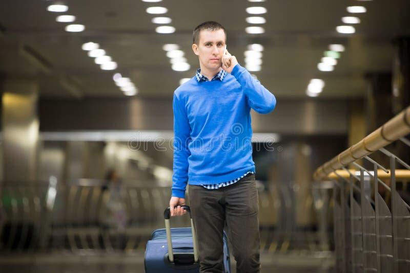 Парень путешественника на телефоне на авиапорте стоковые изображения