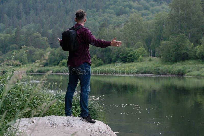 Парень путешественника с рюкзаком в джинсах и рубашке стоит на камне на банке реки горы и смотрит вперед стоковое изображение