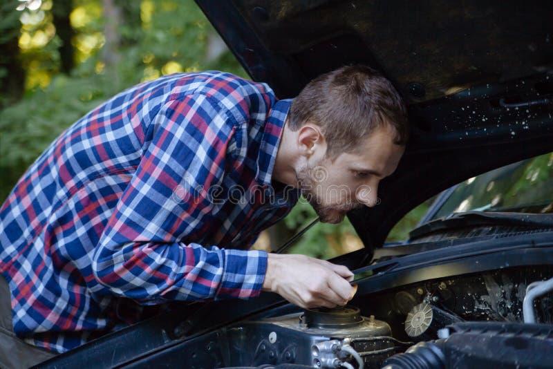 Парень смотрит двигатель автомобиля стоковое изображение rf