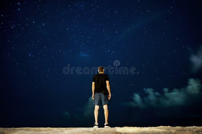 Парень стоит ночью, глядя на звезды вдалеке, задний вид стоковая фотография