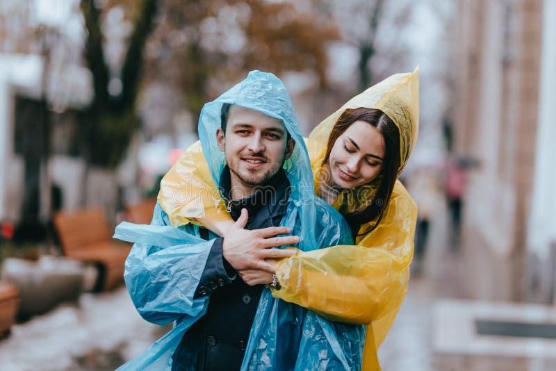 Парень счастливых пар любящий и его девушка одетые в плащах обнимают на улице в дожде стоковое фото rf